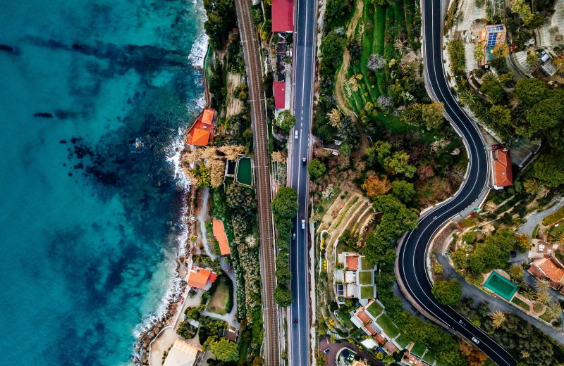 Aerial view of road, highway and railway going along ocean or sea. Drone photography from above in rural Italy